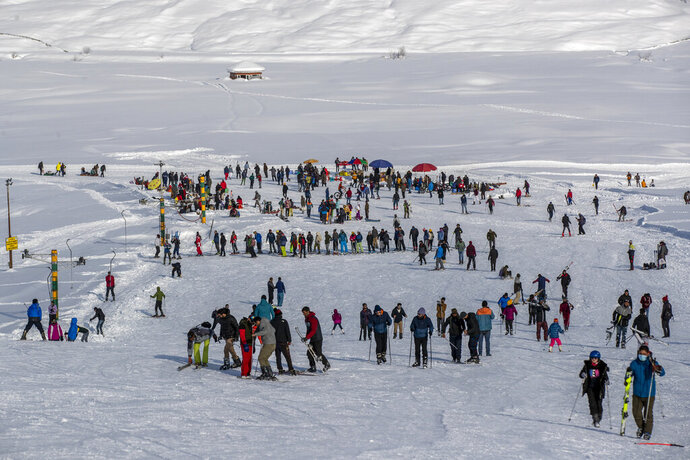 """Indian tourists and locals ski on a slope in Gulmarg, northwest of Srinagar, Indian controlled Kashmir, Monday, Jan. 11, 2021. Snow this winter has brought along with it thousands of locals and tourists to Indian-controlled Kashmir's high plateau, pastoral Gulmarg, which translates as """"meadow of flowers."""
