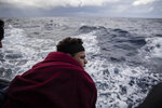 In this Monday Jan. 13, 2020 photo, a Moroccan boy watches the sea on board the Spanish NGO Open Arms vessel, as the NGO waits for the authorities to allow them to enter in the nearest safe port with the 118 people who were rescued off the Libyan coast on Friday, international waters, Central Mediterranean sea. (AP Photo/Santi Palacios)