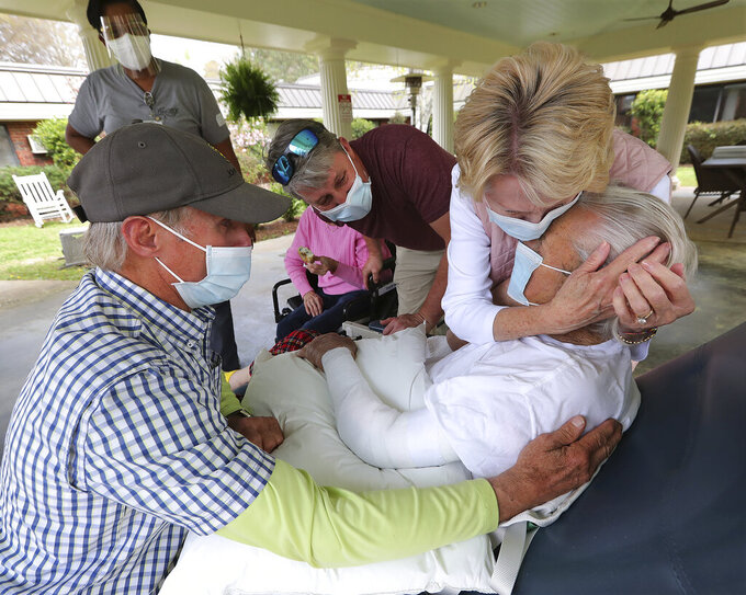 Bonnie McBrome, right,  and her brother Erwin Bryan, left,  emotionally embrace their father Doyle Bryan, 86, for the first time since COVID restrictions were put in place as loved ones begin in person family visits at Westbury Medical Care and Rehab on Tuesday, March 30, 2021, in Jackson, Ga. Looking on at center is grandson Brian Abernathy. The facility was one of the hardest hit in Georgia losing 34 residents and 1 staff member to the pandemic. (Curtis Compton/Atlanta Journal-Constitution via AP)