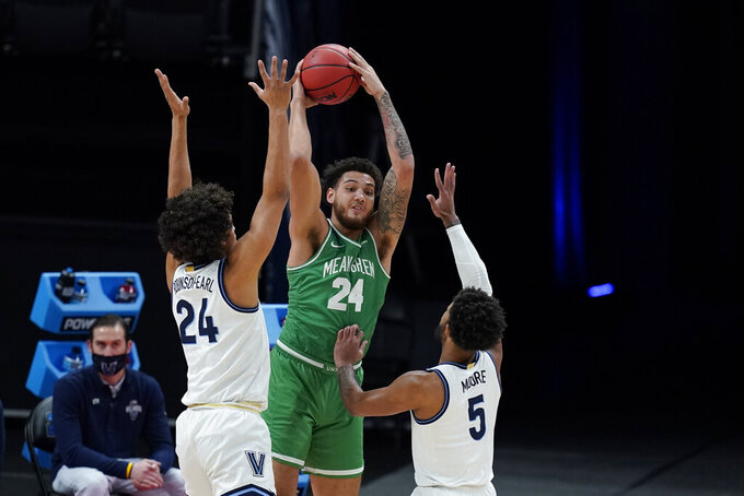 North Texas's Zachary Simmons (24) makes a pass against Villanova's Jeremiah Robinson-Earl (24) and Justin Moore (5) during the first half of a second-round game in the NCAA men's college basketball tournament at Bankers Life Fieldhouse, Sunday, March 21, 2021, in Indianapolis. (AP Photo/Darron Cummings)