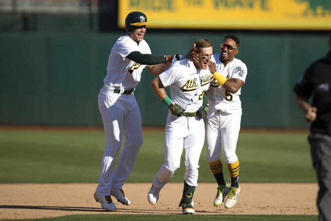 From left to right, Oakland Athletics center fielder Starling Marte, left fielder Mark Canha and second baseman Tony Kemp celebrate defeating the Houston Astros in a baseball game in Oakland, Calif., Sunday, Sept. 26, 2021. The Athletics won 4-3. (AP Photo/John Hefti)