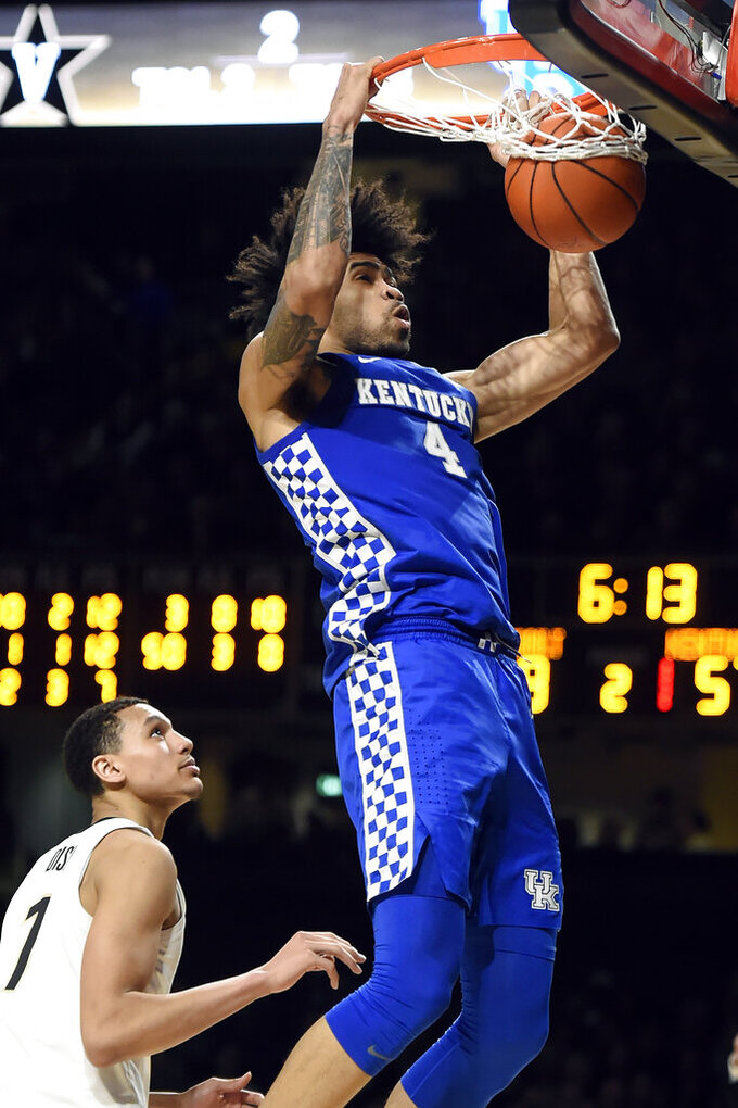 Kentucky forward Nick Richards (4) dunks the ball in front of Vanderbilt forward Dylan Disu (1) during the second half of an NCAA college basketball game Tuesday, Feb. 11, 2020, in Nashville, Tenn. Kentucky won 78-64. (AP Photo/Mark Zaleski)