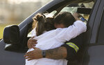Sarai Aranda hugs her son, who was part of the cleanup crew to empty out the remaining chemicals in the open tanks, as the Intercontinental Terminals Company petrochemical fire reignited, Friday, March 22, 2019, in Deer Park, Texas.  The efforts to clean up a Texas industrial plant that burned for several days this week were hamstrung Friday by a briefly reignited fire and a breach that led to chemicals spilling into the nearby Houston Ship Channel. (Godofredo A. Vasquez/Houston Chronicle via AP)