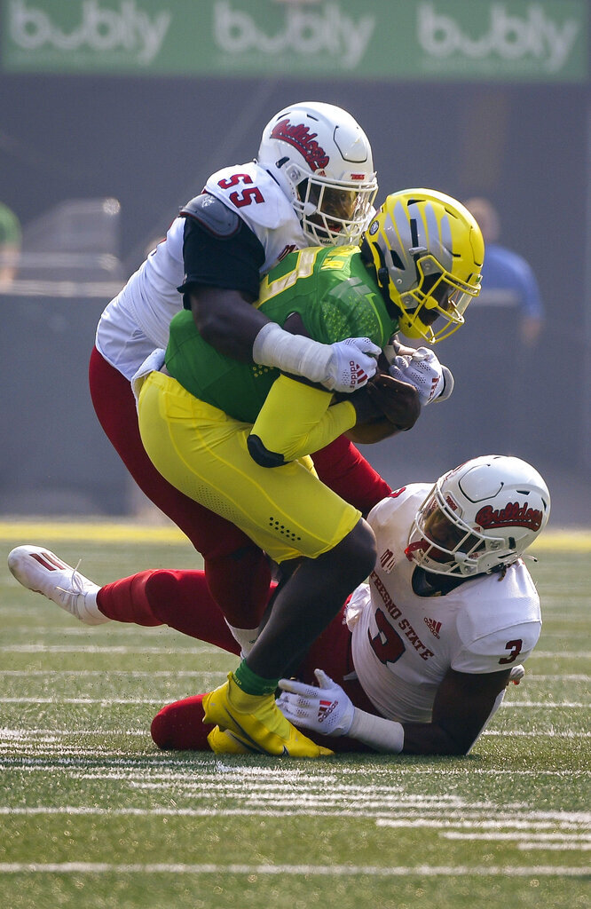 Oregon quarterback Anthony Brown (13) is wrapped up by Fresno State tackle Leonard Payne (55) and defensive end Aaron Mosby (3) during the first quarter of an NCAA college football game, Saturday, Sept. 4, 2021, in Eugene, Ore. (AP Photo/Andy Nelson)