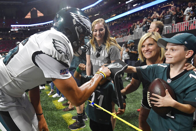 Philadelphia Eagles wide receiver Mack Hollins (16) fist bumps a eagles fan after warming up before the first half of an NFL football game against the Atlanta Falcons, Sunday, Sept. 15, 2019, in Atlanta. (AP Photo/John Amis)