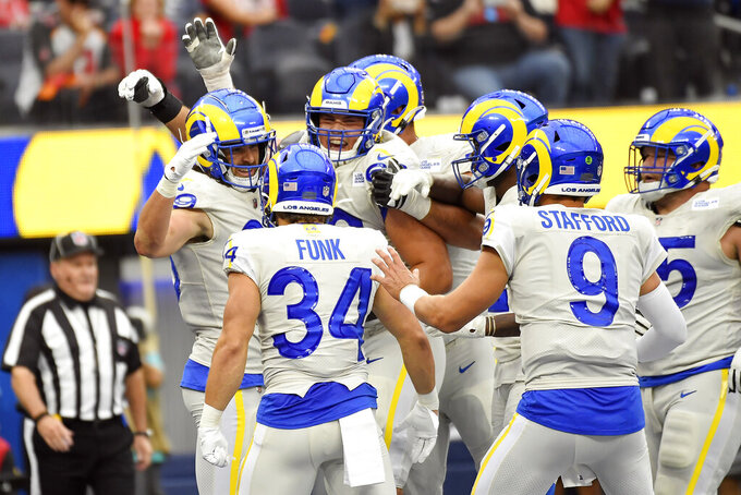 Los Angeles Rams tight end Tyler Higbee, left, celebrates his touchdown catch with teammates during the first half of an NFL football game against the Tampa Bay Buccaneers Sunday, Sept. 26, 2021, in Inglewood, Calif. (AP Photo/Kevork Djansezian)