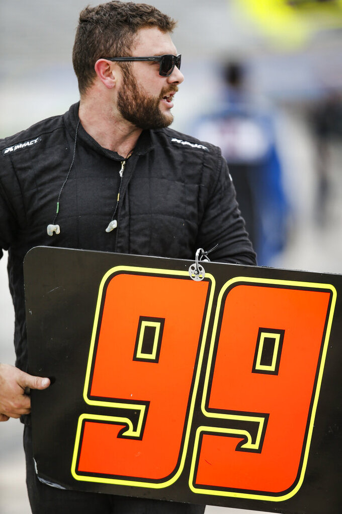 A members of Tommy Joe Martins' pit crew prepares their pit box sign before a NASCAR auto race at Texas Motor Speedway, Saturday, March 30, 2019, in Fort Worth, Texas. (AP Photo/Brandon Wade)