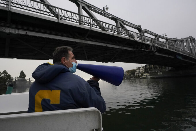 FILE - In this Nov. 19, 2020, file photo, coach Mike Teti speaks into a megaphone toward rowers practicing in the Oakland Estuary in Oakland, Calif. As the Tokyo Games approach, US Rowing is awaiting the results of a months-long assessment commissioned by the U.S. Olympic & Paralympic Committee of its national team programs, including the men's group based in Oakland, where longtime coach Mike Teti is being criticized by some rowers for what they call his intense and intimidating style. (AP Photo/Jeff Chiu, File)