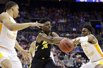 Iowa's Tyler Cook, center, passes between Tennessee's Grant Williams, left and Admiral Schofield in the first half during a second round men's college basketball game in the NCAA Tournament in Columbus, Ohio, Sunday, March 24, 2019.  (AP Photo/Tony Dejak)
