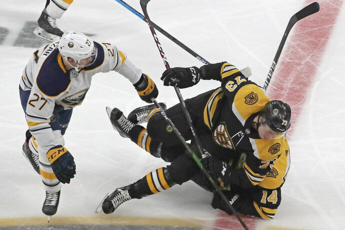 Boston Bruins defenseman Charlie McAvoy (73) crashes into right wing Chris Wagner (14) as Buffalo Sabres center Curtis Lazar (27) watches while chasing the puck during the second period of an NHL hockey game Thursday, Nov. 21, 2019, in Boston. (AP Photo/Elise Amendola)