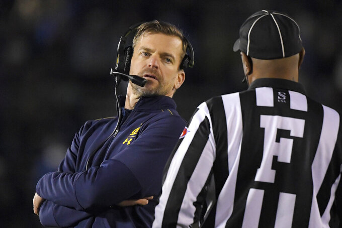 California coach Justin Wilcox, left, talks to an official during the first half of the team's NCAA college football game against UCLA on Saturday, Nov. 30, 2019, in Pasadena, Calif. (AP Photo/Mark J. Terrill)
