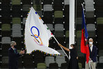 Paris mayor Anne Hidalgo, right, holds the Olympic flag next International Olympic Committee's President Thomas Bach, left, during the closing ceremony in the Olympic Stadium at the 2020 Summer Olympics, Sunday, Aug. 8, 2021, in Tokyo, Japan. (AP Photo/Charlie Riedel)