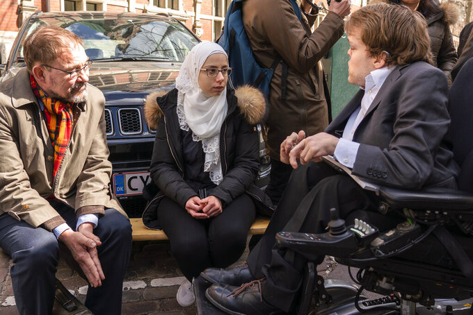 Faeza Satouf, center, talks with her lawyer, Niels-Erik Hansen, left, and a Danish member of Parliament at a meeting with Syrian refugees in Copenhagen, Denmark, Wednesday, April 21, 2021. Ten years after the start of the Syrian civil war, Denmark has become the first European country to start revoking the residency permits of some refugees from the Damascus area, including Satouf's. (AP Photo/David Keyton)