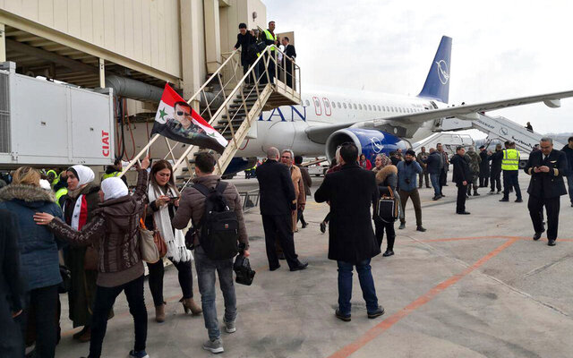 In this photo released by the Syrian official news agency SANA, Syrian officials and journalists disembark a Syrian commercial plane after it landed at Aleppo Airport, Syria, Wednesday, Feb. 19, 2020. The Syrian commercial flight on Wednesday from Damascus, marked the resumption of internal flights between Syria's two largest cities for the first time since 2012. (SANA via AP)
