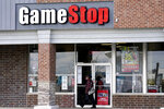 FILE - In this Oct. 15, 2020 file photo, a woman wears a face mask as she walks past a GameStop store in Des Plaines, Ill. Two hedge funds are bowing out of their short positions on the money-losing video game retailer. Citron Research's Andrew Left said in a video posted on YouTube that his company is going to become more judicious in shorting stocks. Melvin Capital is also exiting GameStop, with manager Gabe Plotkin telling CNBC that the hedge fund was taking a significant loss.  (AP Photo/Nam Y. Huh, File)