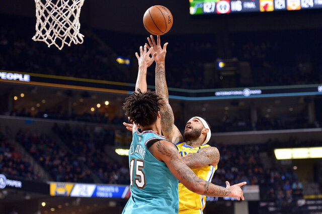 Golden State Warriors center Willie Cauley-Stein, right, shoots against Memphis Grizzlies forward Brandon Clarke (15) in the first half of an NBA basketball game Sunday, Jan. 12, 2020, in Memphis, Tenn. (AP Photo/Brandon Dill)