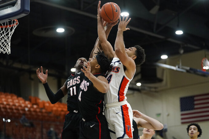 Gonzaga guard Joel Ayayi (11) and guard Aaron Cook (4) and Pepperdine guard Robbie Heath, right, reach for a rebound during the first half of an NCAA college basketball game Saturday, Jan. 30, 2021, in Malibu, Calif. (AP Photo/Ashley Landis)