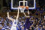 FILE - Stephen F. Austin forward Nathan Bain (23) drives for the game-winning basket against Duke forward Jack White (41) during overtime in an NCAA college basketball game in Durham, N.C., in this Tuesday, Nov. 26, 2019, file photo. Bain provided one of college basketball's signature moments last season, a buzzer-beating layup in overtime to give unheralded Stephen F. Austin a stunning upset over Duke. But that became just a sliver of the story that night. His layup won a game -- and rebuilt a home, rebuilt a school and rebuilt a church, all of it directly impacting the lives of hundreds of Bahamians who have dealt with enormous challenges for the last 14 months and counting. (AP Photo/Gerry Broome, File)