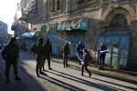 In this Tuesday, Feb. 12, 2019 photo, Palestinian observers, right, watch as children walk past Israeli soldiers on their way to school in the West Bank city of Hebron. Following Israel's expulsion of an international observer force from this volatile West Bank city, Palestinian activists are trying to fill the void by launching their own patrols to document alleged Israeli settler violence. (AP Photo/Majdi Mohammed)