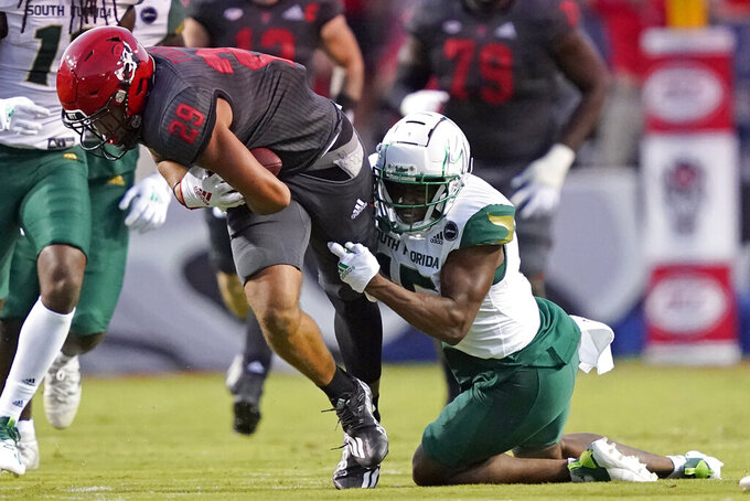 South Florida defensive back Jayden Curry (15) tackles North Carolina State wide receiver Christopher Toudle (29) during the first half of an NCAA college football game in Raleigh, N.C., Thursday, Sept. 2, 2021. (AP Photo/Gerry Broome)