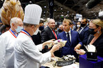 French President Emmanuel Macron tastes goods as he visits the International Catering, Hotel and Food Trade Fair (SIRHA) in Lyon, central France, Monday Sept. 27, 2021.(Denis Balibouse/Pool via AP)