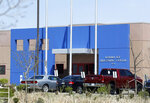 FILE - In this April 15, 2017, file photo, vehicles are parked outside the entrance to the GEO Group's immigrant detention facility in Aurora, Colo. U.S. immigration authorities say more than 2,200 people exposed to a mumps outbreak in at least two detention facilities have been quarantined. Immigration and Customs Enforcement said Tuesday, March 12, 2019, that the quarantine began March 7 at facilities in Pine Prairie, Louisiana, and Aurora, Colorado. (AP Photo/David Zalubowski, File)