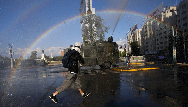 An anti-government protester runs from police water cannons, on the day Chileans vote in a referendum to decide whether the country should replace its 40-year-old constitution, written during the dictatorship of Gen. Augusto Pinochet, in Santiago, Chile, Sunday, Oct. 25, 2020. (AP Photo/Luis Hidalgo)