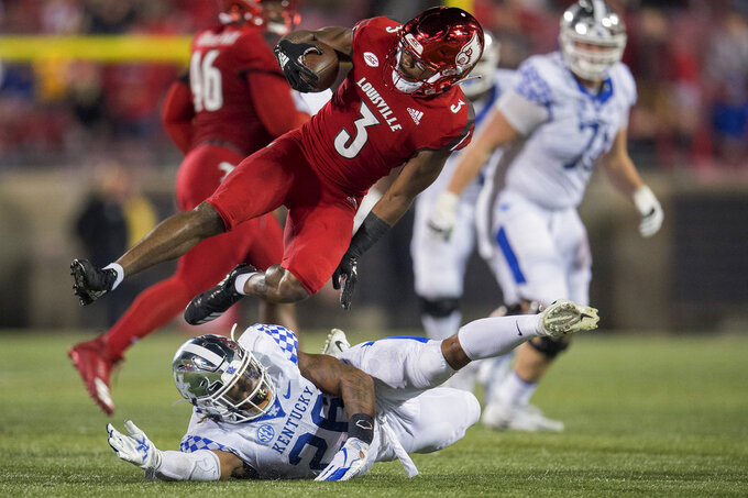 After making an interception, Louisville cornerback Cornelius Sturghill (3) avoids the tackle of Kentucky running back Benny Snell Jr. (26) during the second half of an NCAA college football game in Louisville, Ky., Saturday, Nov. 24, 2018. (AP Photo/Bryan Woolston)