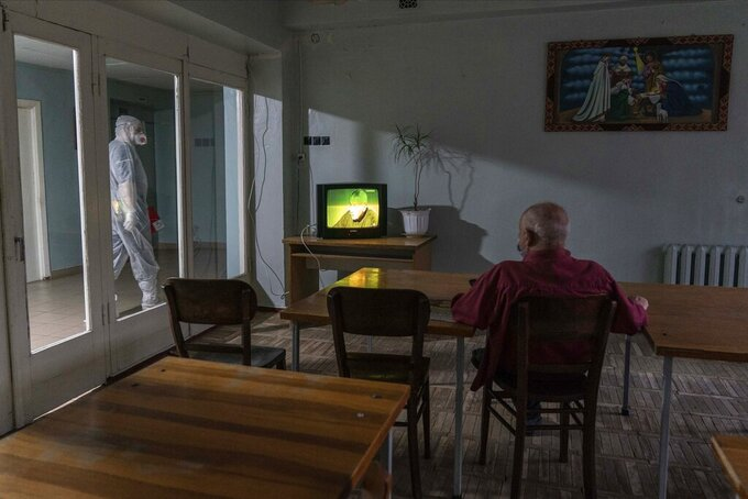 A medical worker walks past a room as a coronavirus patient watches TV at a hospital in Stebnyk, Ukraine, on Tuesday, Sept. 29, 2020. As coronavirus cases increase, every bed in the hospital in this city in western Ukraine is in use and its chief doctor is watching the surge with alarm and anguish. (AP Photo/Evgeniy Maloletka)