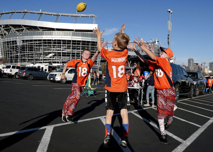 In this Oct. 24, 2016, photo, kids play football outside Mile High Stadium prior to an NFL football game between the Houston Texans and the Denver Broncos, Monday, Oct. 24, 2016, in Denver. USA Football has unveiled a council that will oversee the implementation of its Football Development Model for the sport to help parents, coaches and program leaders provide what players need to develop and grow as athletes and people through football participation. (AP Photo/Joe Mahoney, File)