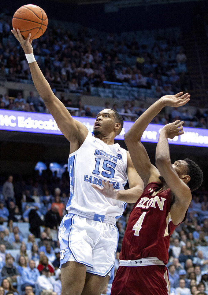 North Carolina's Garrison Brooks (15) attempts a shot ahead of Elon's Marcus Sheffield II (4) during the first half of an NCAA college basketball game in Chapel Hill, N.C., Wednesday, Nov. 20, 2019. (AP Photo/Ben McKeown)