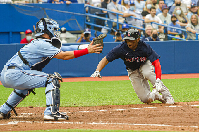 Boston Red Sox's Rafael Devers (11) dives in to home place during the fourth inning of a baseball game against the Toronto Blue Jays, Sunday, Aug. 8, 2021 in Toronto. (Christopher Katsarov/The Canadian Press via AP)