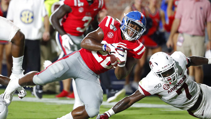Mississippi running back Scottie Phillips (22) dives next to Arkansas defensive back Joe Foucha (7) during the second half of their NCAA college football game Saturday, Sept. 7, 2019, in Oxford, Miss. (AP Photo/Rogelio V. Solis)
