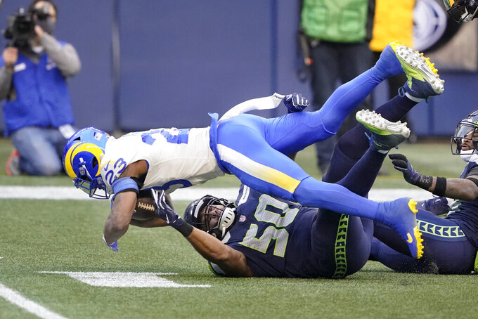 Los Angeles Rams running back Cam Akers (23) flips forward as Seattle Seahawks outside linebacker K.J. Wright (50) defends during the first half of an NFL wild-card playoff football game, Saturday, Jan. 9, 2021, in Seattle. (AP Photo/Ted S. Warren)