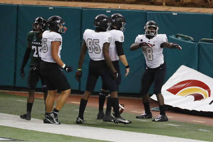 UNLV running back Charles Williams (8) performs a mock hula dance after scoring a touchdown against Hawaii in the second half of an NCAA college football game Saturday, Dec. 12, 2020, in Honolulu. (AP Photo/Marco Garcia)