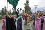 FILE- In this Aug. 9, 2019 file photo, Kashmiri women shout slogans protesting against India's decision to strip Kashmir of its autonomy as they march on a street after Friday prayers in Srinagar, Indian controlled Kashmir. The beautiful Himalayan valley is flooded with soldiers and roadblocks of razor wire. Phone lines are cut, internet connections switched off, politicians arrested. Narendra Modi, the prime minister of the world's largest democracy has clamped down on Kashmir to near-totalitarian levels. (AP Photo/ Dar Yasin, file)