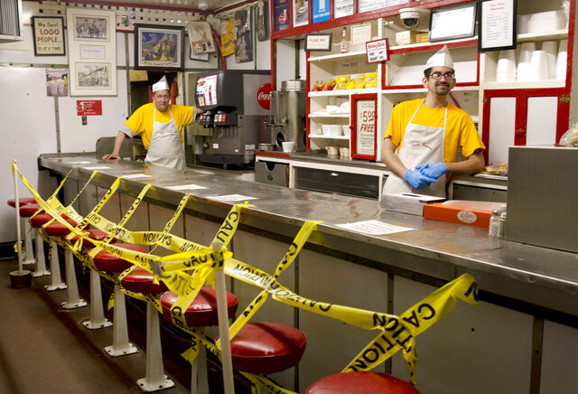 Texas Tavern employees Chris Dobe, left, and Nick Moore wait for take out orders on Monday night, March 30, 2020. Though customers are tipping well, and the diner is still open 24-7, Moore said they are making a quarter to a third less than what they normally do in tips. (Heather Rousseau/The Roanoke Times via AP)