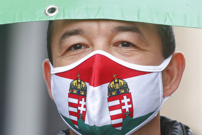 A man wears a mask in the colors of the Hungarian flag during a protest against COVID-19 restrictions in Budapest, Hungary, Monday, March 15, 2021. Hungarians gathered on the country's national day to protest against the current lockdown measures after new restrictive measures were introduced by the Hungarian government last week aiming to slow a record-breaking wave of COVID-19 hospitalizations and deaths. (AP Photo/Laszlo Balogh)