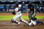 Atlanta Braves' Ozzie Albies (1) dives in to score on a hit by Dansby Swanson as Miami Marlins catcher Jorge Alfaro (38) reaches for the throw during the fifth inning in Game 3 of a baseball National League Division Series, Thursday, Oct. 8, 2020, in Houston. (AP Photo/David J. Phillip)
