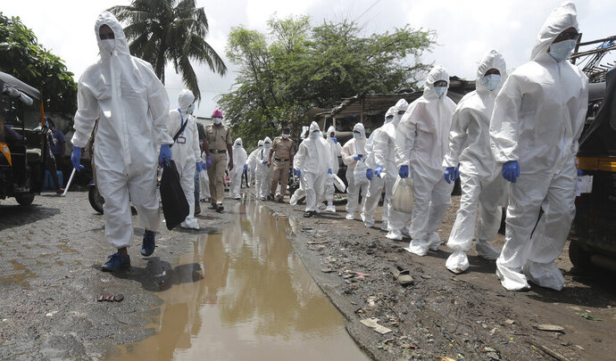 Health workers escorted by policemen arrive to screen people for COVID-19 symptoms at a slum in Mumbai, India, Friday, July 10, 2020. India has overtaken Russia to become the third worst-affected nation by the coronavirus pandemic. (AP Photo/Rafiq Maqbool)