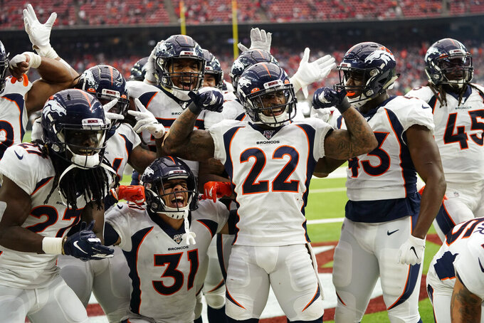 Denver Broncos strong safety Kareem Jackson (22) celebrates his interception with teammates during the second half of an NFL football game against the Houston Texans Sunday, Dec. 8, 2019, in Houston. (AP Photo/David J. Phillip)