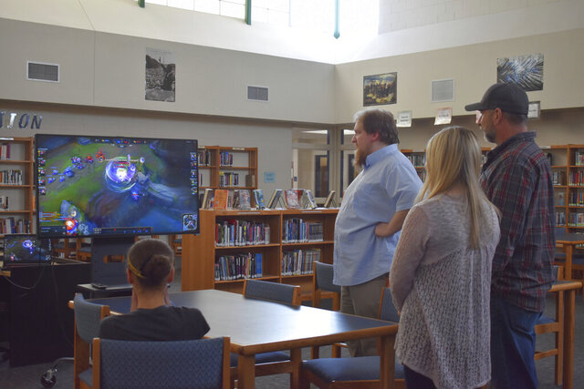 Students, parents and Clinton High School staff gather in the library to watch the March 4 League of Legends match by the Clinton Cougars esports team. (Austin Montgomery/The Beloit Daily News via AP)