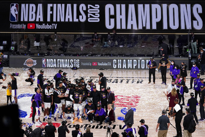 The Los Angeles Lakers players and coaches celebrate after the Lakers defeated the Miami Heat 106-93 in Game 6 of basketball's NBA Finals Sunday, Oct. 11, 2020, in Lake Buena Vista, Fla. (AP Photo/John Raoux)