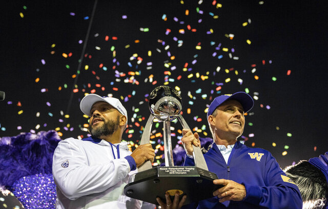 Washington defensive coordinator Jimmy Lake, left, and head coach Chris Petersen lift the Las Vegas Bowl trophy after the team defeated Boise State 38-7 in the Las Vegas Bowl NCAA college football game, Saturday, Dec. 21, 2019, in Las Vegas. Lake is taking over as head coach as Petersen is stepping down after six seasons. (Dean Rutz/The Seattle Times via AP)