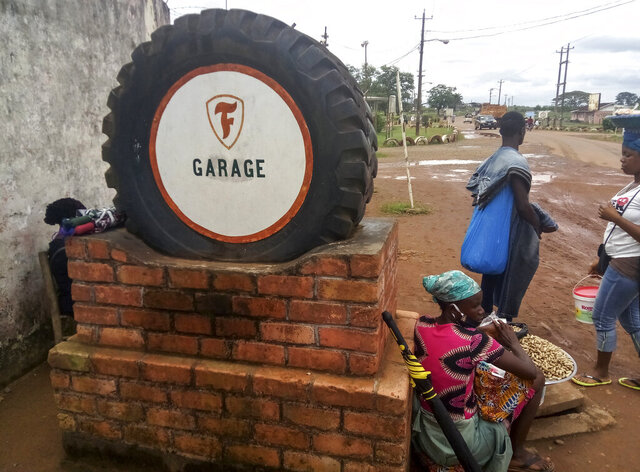 A tyre is used to mark the entrance to Firestone's garage in the town of Harbel, Liberia Saturday, July 18, 2020. The rubber industry in Liberia has gotten so bad that some farmers are cutting down their rubber trees with hopes of producing palm oil instead and Firestone recently announced plans to lay off 374 people with the company citing the impact of the global COVID-19 economic crisis among other factors. (AP Photo/Jonathan Paye-Layleh)
