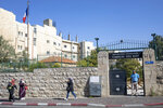 In this Thursday, Oct. 31, 2019 photo, The French tricolor flutters over the Tomb of the Kings, a large underground burial complex dating to the first century BC, as Muslims past bay the iron gate in east Jerusalem neighborhood of Sheikh Jarrah. After several aborted attempts, the French Consulate General has reopened one of Jerusalem's most magnificent ancient tombs to the public for the first time in over a decade, sparking a distinctly Jerusalem conflict over access to an archaeological-cum-holy site in the volatile city's eastern half. (AP Photo/Ariel Schalit)