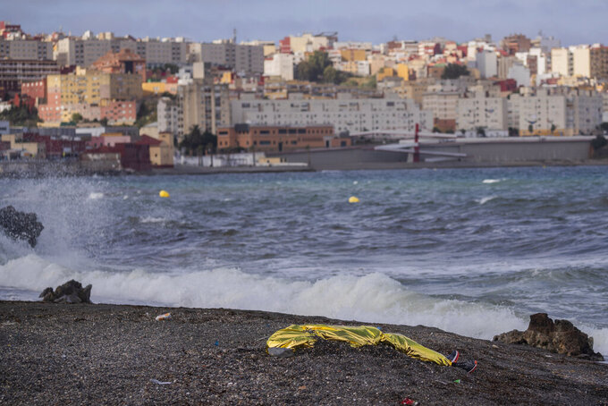 The body of a young man covered with an emergency blanket after being recovered by Spanish police from waters near the border between Morocco and Spain's north African enclave of Ceuta, Thursday, May 20, 2021. Thousands of migrants jumped or swam around a border fence to reach European soil this week after Morocco loosened its border patrols. (AP Photo/Bernat Armangue)