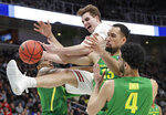 Wisconsin forward Nate Reuvers, top, reaches for a rebound over Oregon forward Paul White, second from right, and guard Ehab Amin (4) during the second half a first-round game in the NCAA men's college basketball tournament, Friday, March 22, 2019, in San Jose, Calif. (AP Photo/Chris Carlson)