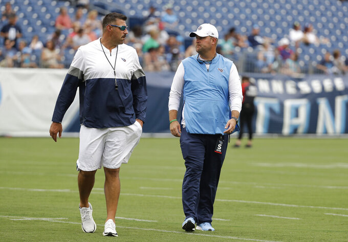 """FILE - In this Aug. 3, 2019, file photo, Tennessee Titans coach Mike Vrabel, left, and general manager Jon Robinson walk on the field before a practice in Nissan Stadium during NFL football training camp in Nashville, Tenn. Robinson, hired in January 2016 to rebuild a team that won five games combined the previous two seasons, finds himself needing to retool the roster for Vrabel. """"We have to add pieces to the team,"""" Robinson said. """"We have a lot of good football players on this football team that have bought into the philosophy of how we want to play the game, to the culture that we have here in Nashville, and we've got to continue to add pieces to this core."""" (AP Photo/Mark Humphrey, File)"""