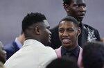 Duke's RJ Barrett, center, talks to Zion Williamson, as Oregon's Bol Bol, back, looks elsewhere before the NBA basketball draft Thursday, June 20, 2019, in New York. (AP Photo/Julio Cortez)
